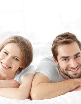 smiling couple on bed