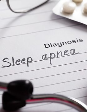 Sleep apnea diagnosis on white paper surrounded by medical items