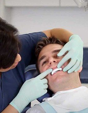 Dentist checking fit of oral appliance