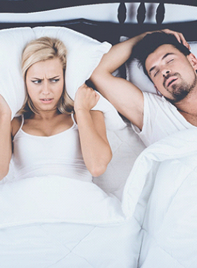 Man snoring in bed while wife blocks ears with pillow