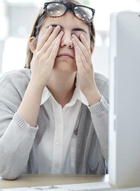 Tired woman at work rubbing her eyes