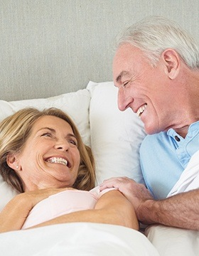 Woman smiling up at man in bed
