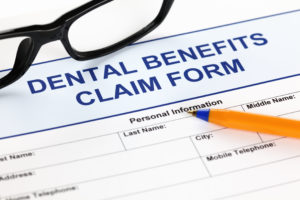 Dental insurance benefits claim form with pen and glasses